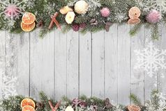 Christmas fir branches with Christmas fruits, white snowflakes as a border against a wood background stock photography