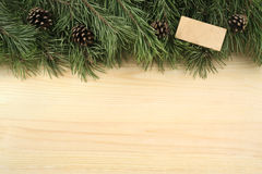 Christmas fir branches, bumps and wooden plate on a wooden background. Royalty Free Stock Photos