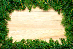 Christmas fir branches frame on wooden board Royalty Free Stock Photo