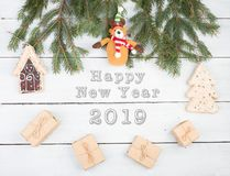Christmas fir branches, gift boxes, gingerbread house, Christmas tree, Teddy bear and text. `Happy New Year 2019` on white wooden background royalty free stock images