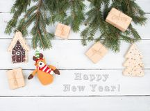 "Christmas fir branches, gift boxes, gingerbread house, Christmas tree, Teddy bear and text ""Happy new year. "" on white wooden background royalty free stock photo"