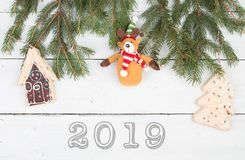 Christmas fir branches, gingerbread house, Christmas tree, Teddy bear and text. `2019` on white wooden background stock photos