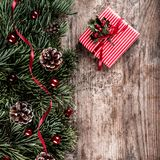 Christmas fir branches on holiday wooden background with gift boxes, pine cones, red decoration. Xmas and New Year theme. Flat lay, top view royalty free stock photography