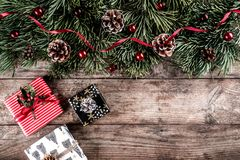 Christmas fir branches on holiday wooden background with gift boxes, pine cones, red decoration. Xmas and New Year theme. Flat lay, top view stock image