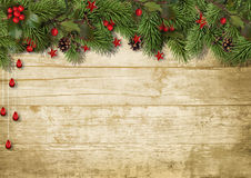 Christmas fir branches and holly on wood background Royalty Free Stock Image