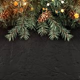 Christmas Fir branches with lights on dark black background. Xmas and Happy New Year card, bokeh, sparking, glowing. Flat lay, top view, wide composition stock image