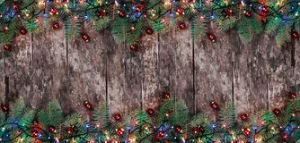 Christmas Fir branches with lights and red decorations on wooden background. Xmas and Happy New Year composition. royalty free stock photography