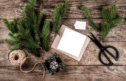 Christmas fir branches, paper card note, scissors and skein of jute on wooden background for decorated Christmas card. Xmas and Happy New Year theme. Flat lay royalty free stock photography