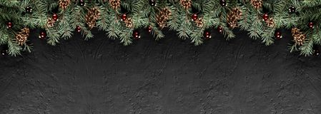 Christmas Fir branches with pine cones on dark black background. Xmas and Happy New Year card, bokeh, sparking, glowing. Flat lay, top view, wide composition stock images