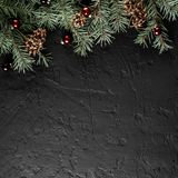 Christmas Fir branches with pine cones on dark black background. Xmas and Happy New Year card, bokeh, sparking, glowing. Flat lay, top view royalty free stock images