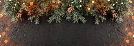 Christmas Fir branches with pine cones on dark holiday background with light. Xmas and Happy New Year theme. Flat lay, top view, wide composition royalty free stock photography