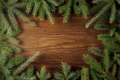 Christmas fir-tree backgrounds with green branches on rustic wooden background. Royalty Free Stock Photo