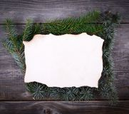 Christmas Fir Tree Border over blank paper on wooden background royalty free stock photography