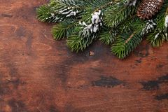 Christmas fir tree branch covered by snow on wood Stock Photography