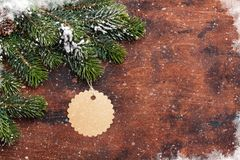 Christmas fir tree branch covered by snow on wood Royalty Free Stock Image