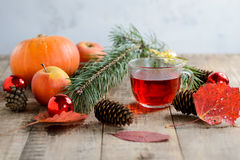Christmas fir tree branch and herbal tea with toys, pumpkins, apples and autumn leaves Royalty Free Stock Photo