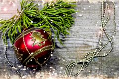 Christmas Fir Tree Branch on rustic wooden board with red ball and copyspace for text. Christmas Card with winter decorati Royalty Free Stock Image