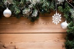 Christmas fir tree branches with decorations on a wooden board. Top view with free space for your text stock images