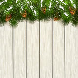 Christmas fir tree branches with snow and cones on white wooden Stock Photography