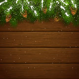 Christmas fir tree branches with snow and cones on wooden backgr. Christmas theme, decorative spruce branches with pine cones and snow on a wooden background Royalty Free Stock Photo