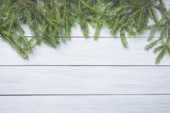 Christmas fir tree branches on the top of white wooden board. Christmas or new year frame for your project with copy space. royalty free stock photos