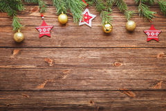 Christmas fir tree branches with wooden stars and Christmas ball. Christmas brown wooden background with wooden stars Stock Images