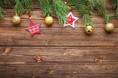 Christmas fir tree branches with wooden stars and Christmas ball. Christmas brown wooden background with wooden stars Royalty Free Stock Photography