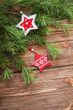 Christmas fir tree branches with wooden stars on a wooden backgr. Christmas brown wooden background with wooden stars Stock Photos