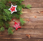 Christmas fir tree branches with wooden stars on a wooden backgr. Christmas brown wooden background with wooden stars Stock Image