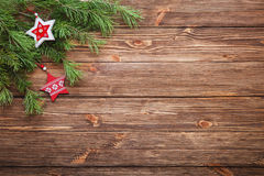 Christmas fir tree branches with wooden stars on a wooden backgr. Christmas brown wooden background with wooden stars Royalty Free Stock Photos