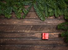 Christmas fir tree brunch and little red gift box on rustic wood Royalty Free Stock Photography