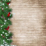 Christmas fir tree with a cardinal on a wooden background. Christmas lights of the Christmas tree and decorations on the wooden background with space for Royalty Free Stock Photography