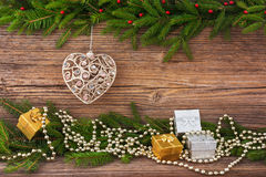 Christmas fir tree, Christmas tree toy, gifts on old wooden board background with copy space. Toned Royalty Free Stock Images