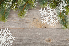 Christmas fir tree and decor on wooden board background. Christmas fir tree and decor covered with snow on wooden board background Royalty Free Stock Photos