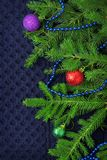 Christmas fir tree with decoration on dark blue knitted wool background Stock Photos