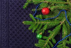Christmas fir tree with decoration on dark blue knitted wool background Stock Image