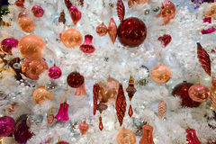 Christmas fir tree with decorations. Christmas white tree with holiday red and orange decorations and lights close up Royalty Free Stock Photo