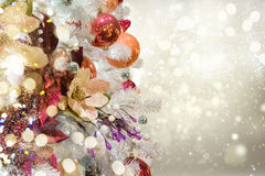 Christmas fir tree with decorations. Christmas white tree with holiday red and orange decorations and lights with copy space on silver bokeh background Stock Photo