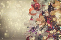 Christmas fir tree with decorations. Christmas white tree with holiday red and orange decorations and lights with copy space on silver bokeh background, retro Royalty Free Stock Images