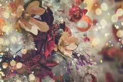 Christmas fir tree with decorations. Christmas white tree with holiday red and orange decorations and lights, retro toned Royalty Free Stock Images