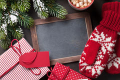 Christmas fir tree, gift, mittens and chalkboard. For your greetings. Top view with copyspace Royalty Free Stock Photos