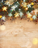 Christmas fir tree with lights of stars on wooden table. Royalty Free Stock Photo