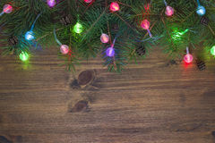 Christmas fir tree with lights on wooden background Royalty Free Stock Images