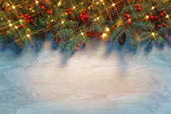 Christmas fir tree with lights on wooden background in dark. Stock Photo
