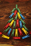 Christmas fir-tree from multi-colored clothespins on the made old wooden brown background Stock Photo