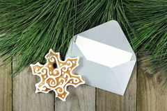 Christmas fir tree, silver envelope with gingerbread on wood Stock Photo