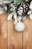 Christmas fir tree with snow and bauble on rustic wooden board Royalty Free Stock Images