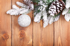 Christmas fir tree with snow and bauble on rustic wooden board Stock Photography