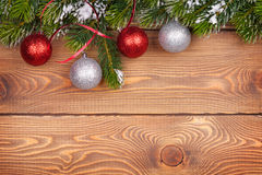 Christmas fir tree with snow and baubles on rustic wooden board. With copy space Stock Photo