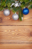 Christmas fir tree with snow and baubles on rustic wooden board. With copy space Royalty Free Stock Photos